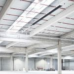 A modern industrial building, under the buildings ceiling a tube heater with condensing technology from Schwank.