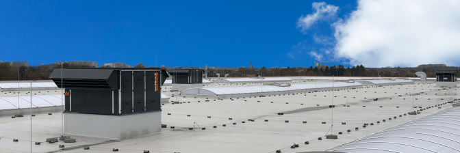 Mehrere RLT-Geräte auf dem Dach eines großen Gebäudes bei blauem Himmel.